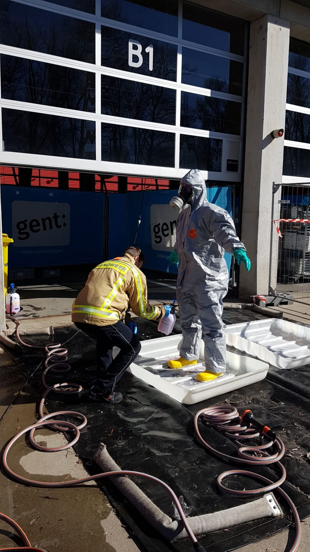 Firefighter decontaminating a person in a HazMat suit