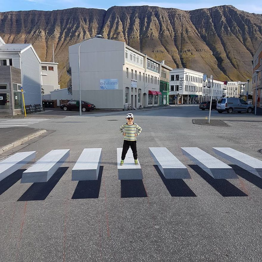 A fake 3D zebra pattern is supposed to slow down cars at crosswalk in India and Iceland.