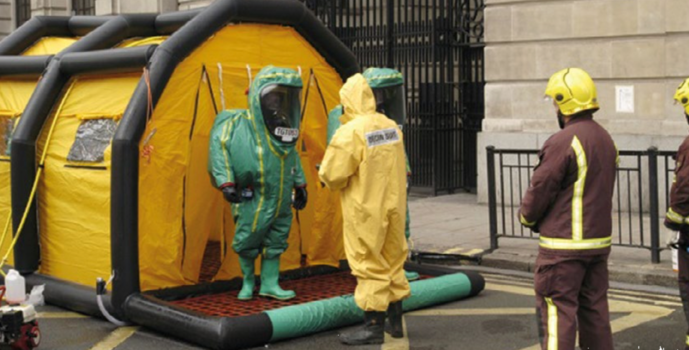 a HazMat tent and first reposnders in full HazMat protective suits.