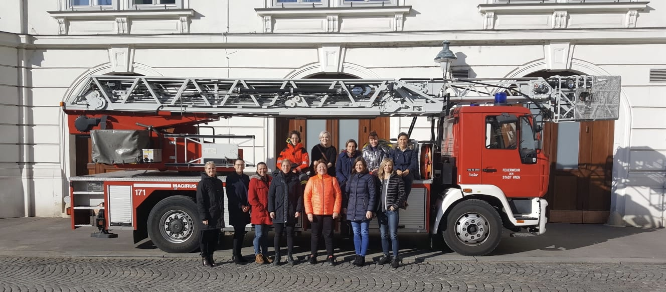 Women commission in front of a firetruck