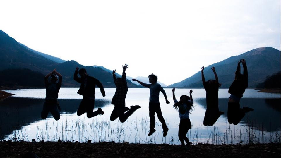 Youth jumping by a lake