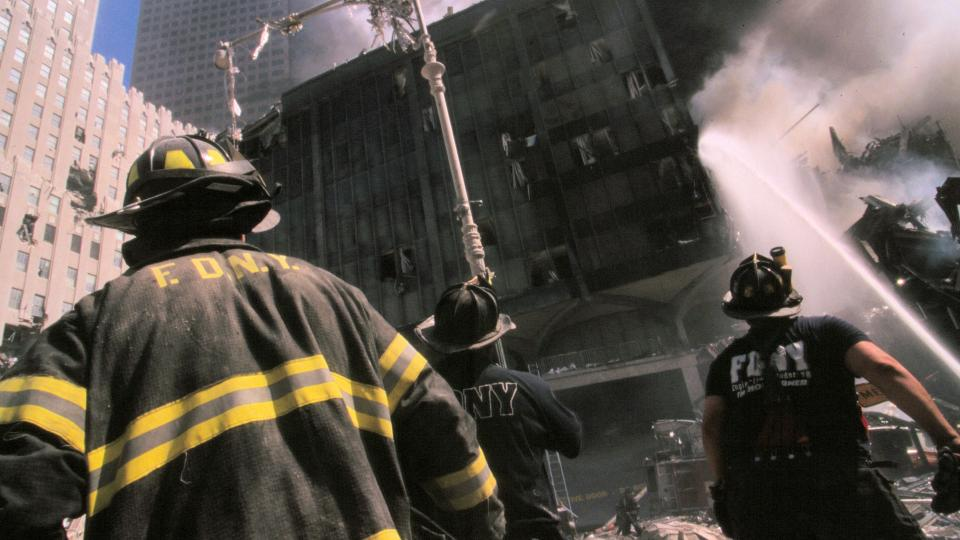 Three New York City firefighters in front of a burning building following the September 11th terrorist attack. Photo by: Wikipedia