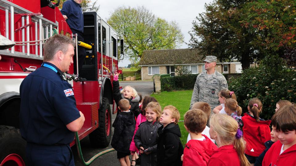 WEST ROW, England -- Watch Manager Ken Cross, left, 423rd Civil Engineer Squadron Fire Department, RAF Alconbury, explains equipment and fire procedures to children from West Row Primary School Nov. 3, 2011. Firefighter Daniel Manning, Staff Sgt. Kyle Dulin and Senior Airman Shayne Anglin (not pictured), all 100th Civil Engineer Squadron Fire Department, visited the local primary school to foster good community relations. (U.S. Air Force photo/Karen Abeyasekere)
