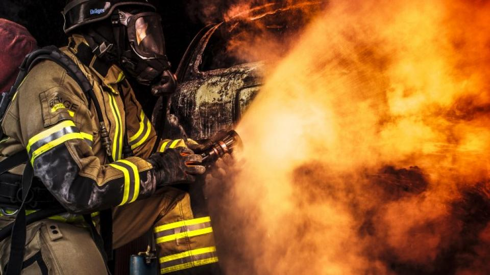 Firefighter using a fog nozzle as a shield against a blaze of fire.