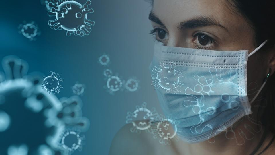 Woman with mask and symbolic corona cells in the air. Photo: Pixabay.com