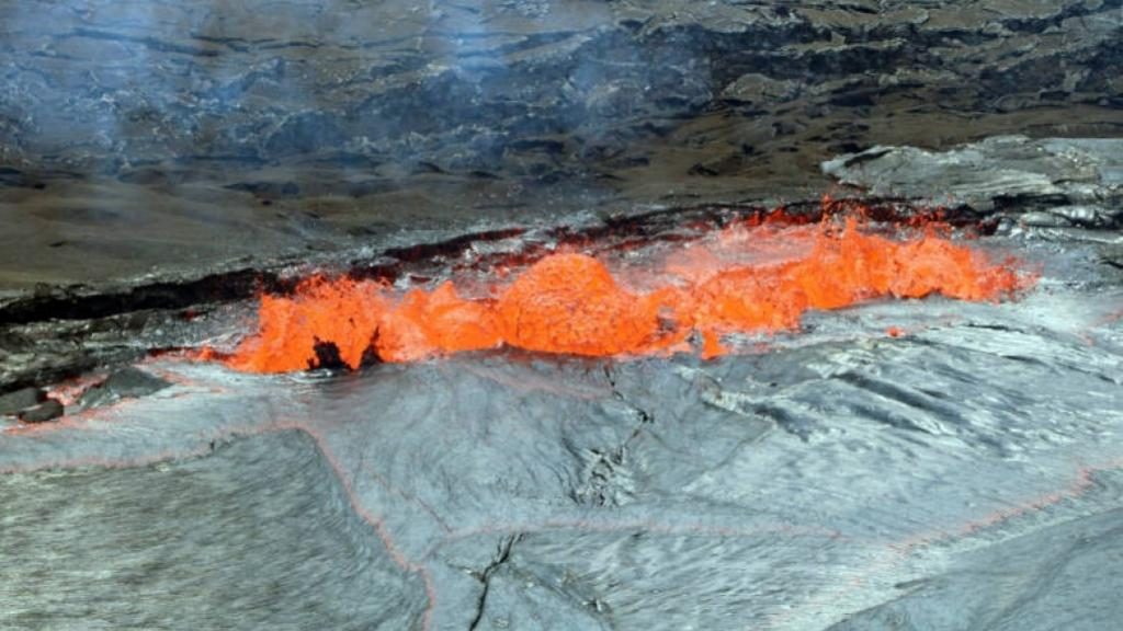 This April 22, 2018, photo provided by the U.S. Geological Survey shows a line of spattering along a lava lake margin with spatter being ejected well above the level of the Halema'uma'u Crater floor and occasional small bits landing on the rim with a piece of the thin, flexible crust on the lava lake being lifted and torn by a bubble burst at left in Kilauea Volcano in Hawaii Volcanoes National Park on Hawaii's Big Island.