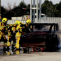 Three Belgian firefighters in turnout gear practice putting out a fire on a burning vehicle.